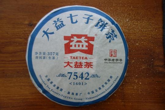 """1601-7542 7542是勐海茶廠出產量最大的青餅,以肥壯茶箐為裡,幼嫩芽葉為撒面. 用料以4級為主, 選取勐海茶區1到3年的春茶來作拼配. 香氣純正, 帶持久的果香. 滋味濃郁, 回甘強. 口感層次分明. 7542被市場稱為""""評判普洱生茶品質的標準產品"""" 7542 is Menghai Tea Factory's most produced raw pu'er cake. It uses fat, thick material for inner material, and sprinkles young tender buds to make up the cake's face. 7542 uses 1-3 year old spring material from the Menghai tea region to create it's blend. The average grade leaf in the cake is grade 4. 7542 has a pure, mellow fragrance, and long lasting fruit notes. The tea's flavors are very strong, with a powerful returning sweetness. Flavors within the tea are diverse and complex. In the pu'er market this tea is known as the """"standard quality for judging raw pu'er teas."""""""